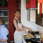 Die thailändische Köchin Rassamee steht im Thai-Markt am Herd.