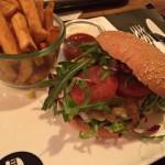 Cheeseburger mit Senf-Gurken-Chutney und Pommes.