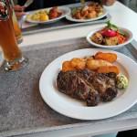 Holzfällersteak mit Bratkartoffeln und Kräuterbutter.