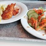 Gebackenes Seelachsfilet frisch aus der Pfanne mit Kartoffelsalat und gemischtem Salat.
