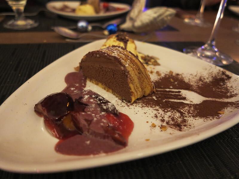 Café Schokoladenmousse im Baumkuchen, serviert mit Erdbeeren/Pflaumen und geeister Pecan-Nuss