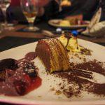Cafe Schokoladenmousse im Baumkuchen, serviert mit Erdbeeren/Pflaumen und geeister Pecan-Nuss (8 Euro)