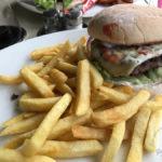 Cheeseburger vom Black-Angus-Rind mit Tomate, Salat, roter Zwiebel und Pommes